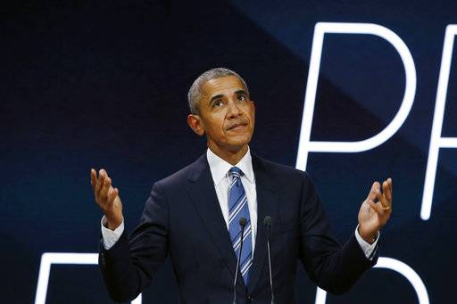 Former U.S. President Obama gestures as he arrives on stage prior to delivering a speech, in Paris, Saturday, Dec. 2, 2017. Former U.S. President Barack Obama is ending a five-day international trip in Paris, where he is lunching with French President Emmanuel Macron and scheduled to give a speech to business leaders. (AP Photo/Thibault Camus)