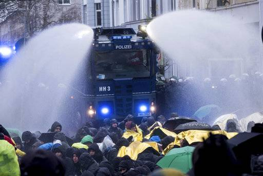 Police use a water cannon to clear a street that is blocked by demonstrators near the congress center where the party convention of the Alternative for Germany, AfD, is held in Hannover, Germany, Saturday, Dec. 2, 2017. (Peter Steffen/dpa via AP)