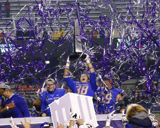 Boise State linebacker Leighton Vander Esch (38), with quarterback Brett Rypien, left, and offensive linesman Mason Hampton (59), holds up the trophy after the team's 17-14 win over Fresno State in an NCAA college football game for the Mountain West Conference championship in Boise, Idaho, Saturday, Dec. 2, 2017.p (AP Photo/Otto Kitsinger)