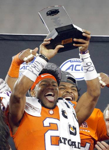 Clemson's Kelly Bryant celebrates with the trophy for winning the game's most valuable player after Clemson's win over Miami in the Atlantic Coast Conference championship NCAA college football game in Charlotte, N.C., Saturday, Dec. 2, 2017. (AP Photo/Bob Leverone)