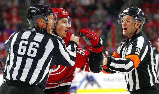 Carolina Hurricanes' Jeff Skinner (53) is subdued by officials during the second period of an NHL hockey game against the Florida Panthers, Saturday, Dec. 2, 2017, in Raleigh, N.C. (AP Photo/Karl B DeBlaker)