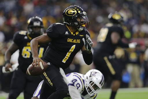 Grambling State quarterback Devante Kincade (1) rolls out and looks to pass in the first quarter against Alcorn during the Southwestern Athletic Conference championship football game in Houston, Texas, Saturday, Dec. 2, 2017. (Tim Warner/Houston Chronicle via AP)