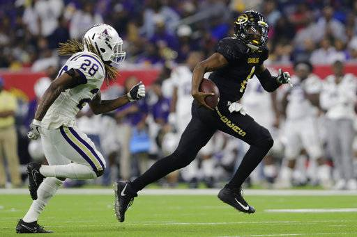 Grambling State quarterback Devante Kincade (1) rushes for a second-quarter touchdown pursued by Alcorn State defensive back Brady Smith (28) during the Southwestern Athletic Conference championship football game in Houston, Texas, Saturday, Dec. 2, 2017. (Tim Warner/Houston Chronicle via AP)