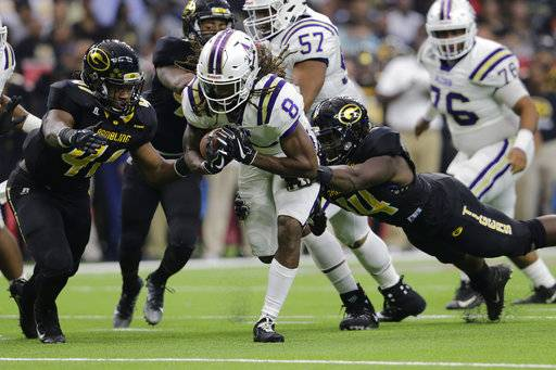 Alcorn State running back De'Lance Turner (8) rushes the ball in the first quarter and is tackled by Grambling State defensive lineman Brandon Varner (44) and linebacker Malcolm Williams (41) during the Southwestern Athletic Conference championship football game in Houston, Texas, Saturday, Dec. 2, 2017. (Tim Warner/Houston Chronicle via AP)