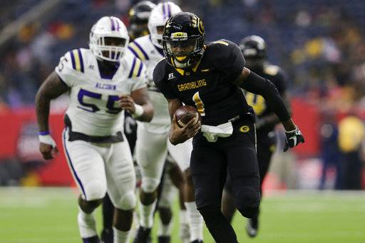 Grambling State quarterback Devante Kincade (1) rushes for a touchdown in the first quarter while pursued by Alcorn State defensive lineman Sterling Shippy (55) during the Southwestern Athletic Conference championship football game in Houston, Texas, Saturday, Dec. 2, 2017. (Tim Warner/Houston Chronicle via AP)