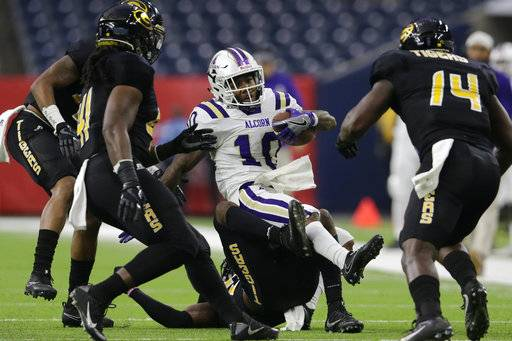 Alcorn State wide receiver Marquis Warford (10) is tackled by Grambling State defensive back Percy Cargo (21) and a group of teammates in the first quarter during the Southwestern Athletic Conference championship football game in Houston, Texas, Saturday, Dec. 2, 2017. (Tim Warner/Houston Chronicle via AP)