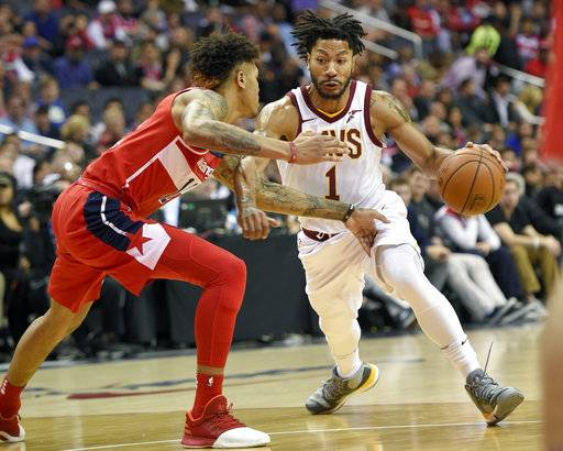 FILE - In this Nov. 3, 2017, file photo, Cleveland Cavaliers' Derrick Rose (1) dribbles against Washington Wizards forward Kelly Oubre Jr., left, during the first half of an NBA basketball game in Washington. Cavaliers coach Tyronn Lue says the team's communication with embattled point guard Rose has been positive. Rose is away from the team because of a personal matter. He also has been sidelined by a sprained left ankle. (AP Photo/Nick Wass, File)