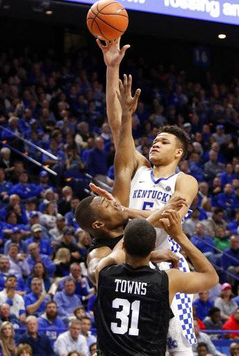Kentucky's Kevin Knox, top, shoots while pressured by Harvard's Chris Lewis and Seth Towns (31) during the second half of an NCAA college basketball game, Saturday, Dec. 2, 2017, in Lexington, Ky. Knox led Kentucky with 20 points in Kentucky's 79-70 win.(AP Photo/James Crisp)