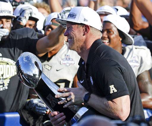 Central Florida head coach Scott Frost holds the winning trophy after defeating Memphis in the American Athletic Conference championship NCAA college football game, Saturday, Dec. 2, 2017, in Orlando, Fla. Central Florida won in overtime 62-55. (AP Photo/John Raoux)