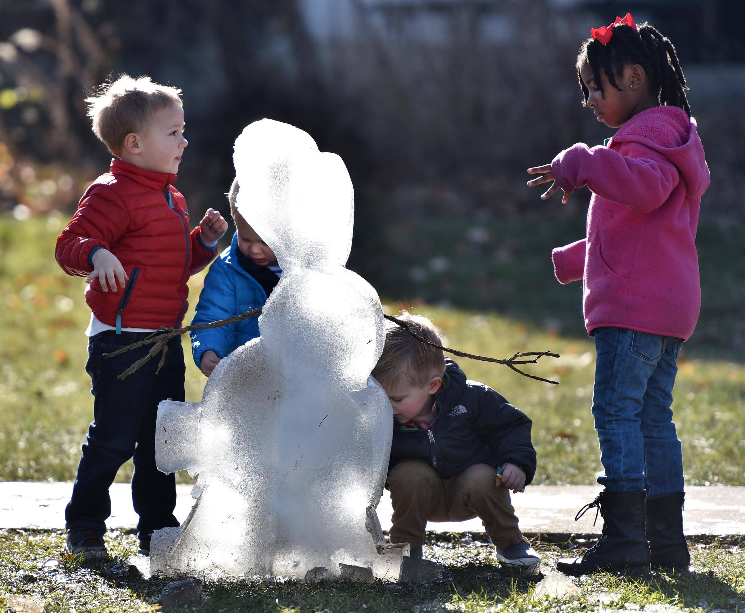 Children play around an ice sculpture Sunday at the Lights of Lisle Festival at Station Park in Lisle. The two-day festival featured hayrides, holiday music and a visit from Santa and Mrs. Claus.