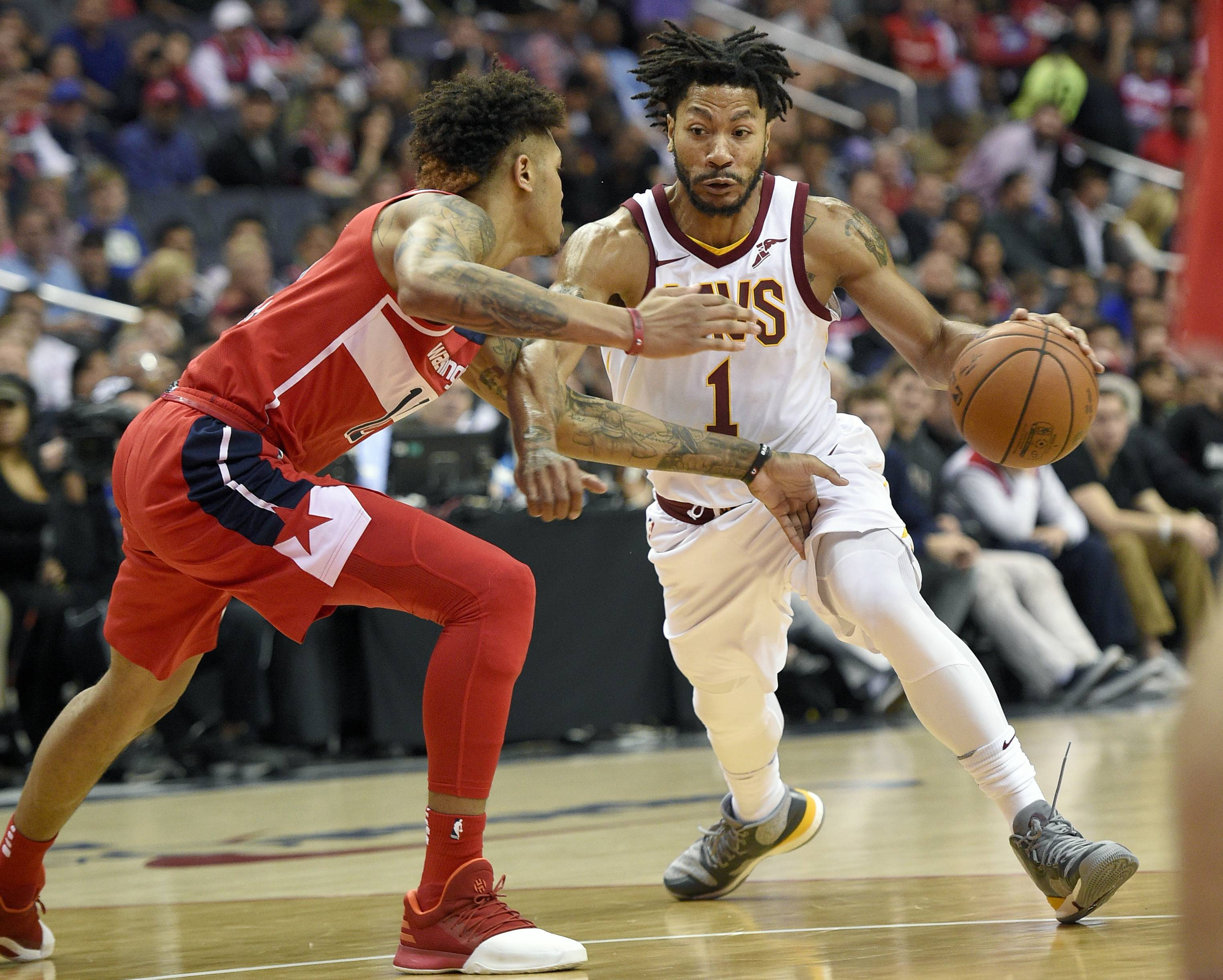 FILE - In this Nov. 3, 2017, file photo, Cleveland Cavaliers' Derrick Rose (1) dribbles against Washington Wizards forward Kelly Oubre Jr., left, during the first half of an NBA basketball game in Washington. Cavaliers coach Tyronn Lue says the team's communication with embattled point guard Rose has been positive. Rose is away from the team because of a personal matter. He also has been sidelined by a sprained left ankle.
