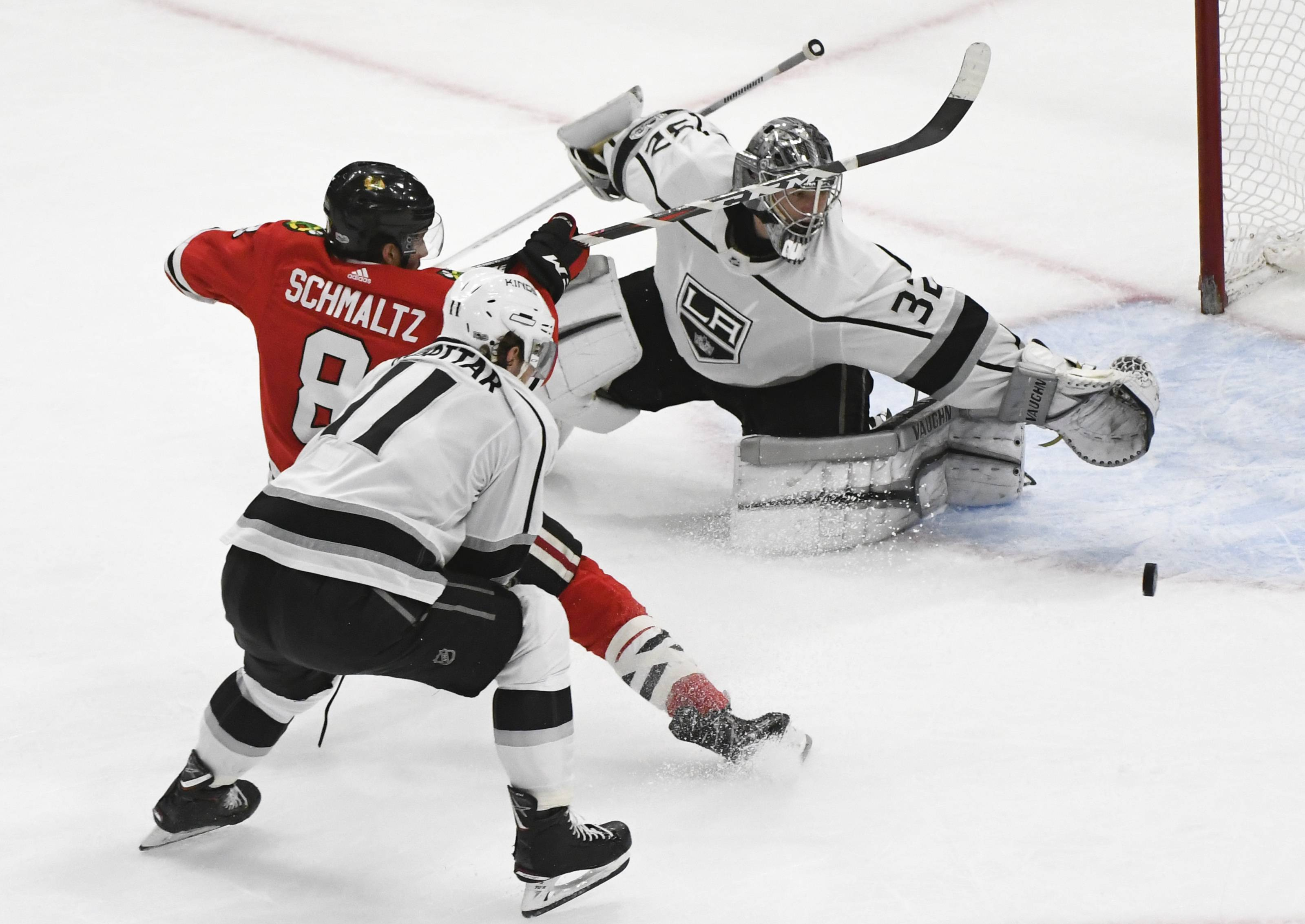 Chicago Blackhawks center Nick Schmaltz (8) shoots as Los Angeles Kings goalie Jonathan Quick (32) defends while center Anze Kopitar (11) helps on defense during the second period of an NHL hockey game Sunday Dec. 3, 2017, in Chicago. (AP Photo/Matt Marton)