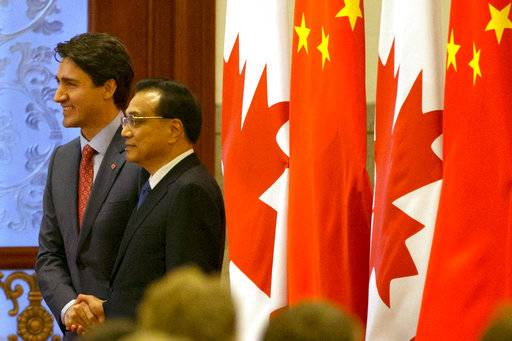 Canadian Prime Minister Justin Trudeau, left, poses for photos with Chinese Premier Li Keqiang during a welcome ceremony held at the Great Hall of the People in Beijing, China, Monday, Dec. 4, 2017. (AP Photo/Ng Han Guan)