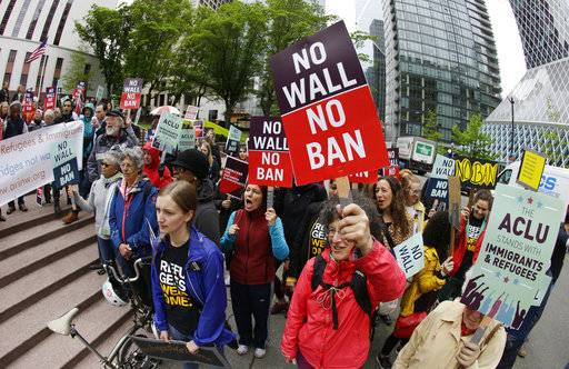 FILE - In this May 15, 2017, file photo, protesters wave signs and chant during a demonstration against President Donald Trump's revised travel ban outside a federal courthouse in Seattle. The fight over the latest version of President Donald Trump's travel ban that targets about 150 million potential travelers from Chad, Iran, Libya, North Korea, Somalia, Syria and Yemen returns to Washington state and Virginia. A three-judge panel of the 9th U.S. Circuit Court of Appeals hears arguments in Seattle on Wednesday, Dec. 6, followed by a full complement of 13 judges at the 4th Circuit in Richmond, Va., on Friday, Dec. 8. (AP Photo/Ted S. Warren, File)