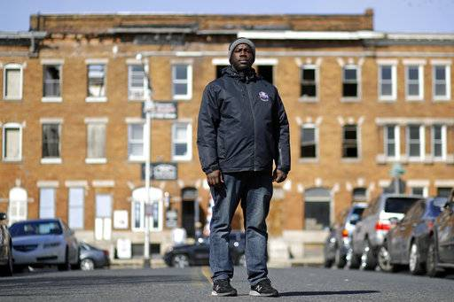 In this March 3, 2017 photo, community outreach worker Kelvin Parker poses for a portrait while walking in the Sandtown-Winchester neighborhood of Baltimore. Parker is one of three outreach workers at U-TURNS, a fledgling initiative with an ambitious goal: to reach teenagers and young adults in west Baltimore and provide an alternative to the streets. (AP Photo/Patrick Semansky)