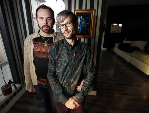 In this Nov. 28, 2017, photo, Charlie Craig and David Mullins are shown in their home in Denver. The Dec. 5, Supreme Court argument about a baker who refused to make a cake for the same-sex couple makes some civil rights lawyers think of South Carolina's Piggie Park barbecue. (AP Photo/David Zalubowski)