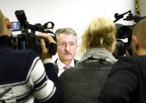 Brandenburg state Interior Minister Karl-Heinz Schroeter is surrounded by media during a news conference in Potsdam, eastern Germany, Sunday, Dec. 3, 2017. German authorities said the suspicious package containing nails that led to a bomb scare on a Christmas market in Potsdam was part of a blackmailing plot against a delivery company. Schroeter told reporters the package was part of a scheme to extort millions of euros from delivery company DHL. (Gregor Fischer/dpa via AP)