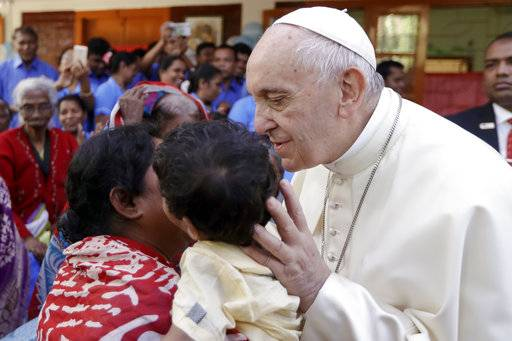 Pope Francis kisses a child as he meets with sick people and staff of the Mother Teresa House in Dhaka's Tejgaon neighborhood, Bangladesh, Saturday, Dec. 2, 2017. (AP Photo/Andrew Medichini, Pool)