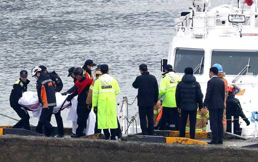 South Korean police officers and rescue workers carry a victim of a boat capsizing at a port in Incheon, South Korea, Sunday, Dec. 3, 2017. A fishing boat collided with a refueling vessel and capsized, the country's coast guard said. (Yun Tae-hyun/Yonhap via AP)