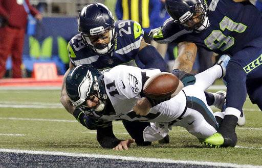 Philadelphia Eagles quarterback Carson Wentz (11) fumbles the ball near the goal line and into the end zone as Seattle Seahawks' Earl Thomas (29) and Sheldon Richardson (91) move in during the second half of an NFL football game, Sunday, Dec. 3, 2017, in Seattle. (AP Photo/John Froschauer)