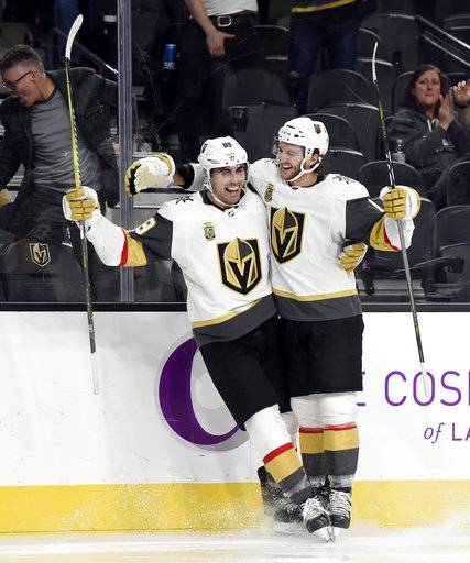 Vegas Golden Knights right wing Alex Tuch (89) celebrates with teammate Colin Miller after scoring a goal against the Arizona Coyotes during the second period of an NHL hockey game, Sunday, Dec. 3, 2017, in Las Vegas. (AP Photo/David Becker)