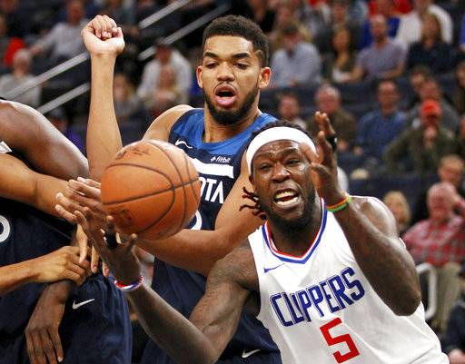 Minnesota Timberwolves forward Karl-Anthony Towns fights for a rebound with Los Angeles Clippers Montrezl Harrell (5) in the second quarter of an NBA basketball game on Sunday, Dec. 3, 2017, in Minneapolis. (AP Photo/Andy Clayton-King)