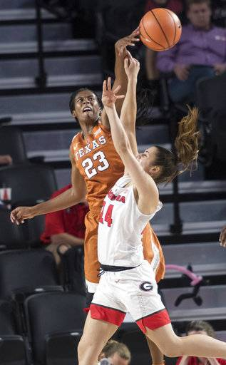 Texas guard Ariel Atkins (23) blocks the shot of Georgia guard Simone Costa during the first half of an NCAA college basketball game, Sunday, Dec. 3, 2017, in Athens, Ga. Texas won 81-53. (AP Photo/John Amis)