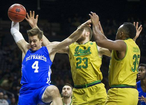 St. Francis (NY)'s Gunnar Olafsson (4) grabs a rebound next to Notre Dame's Martinas Geben (23) and Bonzie Colson (35) during the second half of an NCAA college basketball game Sunday, Dec. 3, 2017, in South Bend, Ind. (AP Photo/Robert Franklin)