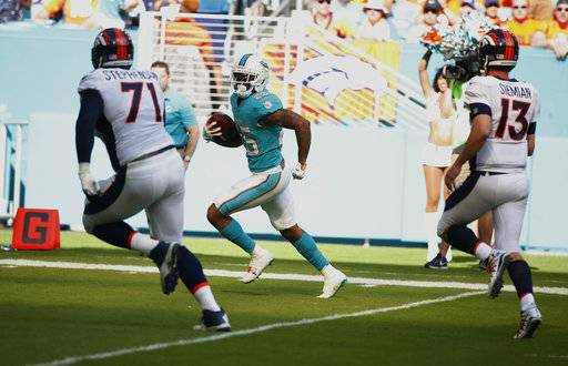 Miami Dolphins cornerback Xavien Howard (25) intercepts a pass by Denver Broncos quarterback Trevor Siemian (13) and runs it for a touchdown during the first half of an NFL football game against the Denver Broncos, Sunday, Dec. 3, 2017, in Miami Gardens, Fla. To the left is Denver Broncos offensive tackle Donald Stephenson (71). (AP Photo/Wilfredo Lee)
