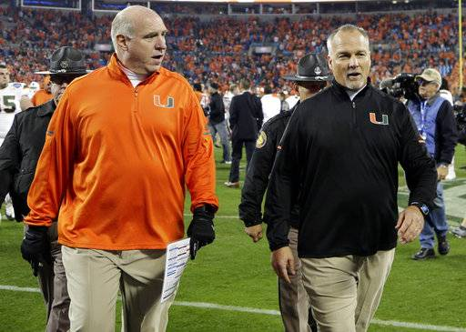 Miami head coach Mark Richt, right, walks off the field after losing to Clemson in the Atlantic Coast Conference championship NCAA college football game in Charlotte, N.C., Saturday, Dec. 2, 2017. (AP Photo/Chuck Burton)