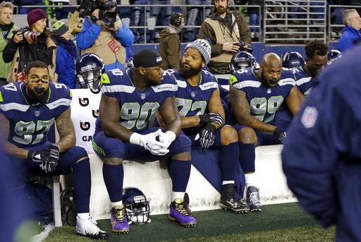 Seattle Seahawks' Michael Bennett (72) sits on the bench with several teammates during the singing of the national anthem, Sunday, Dec. 3, 2017, in Seattle before the team's NFL football game against the Philadelphia Eagles. (AP Photo/Ted S. Warren)