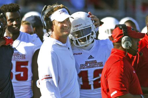 Florida Atlantic head coach Lane Kiffin hugs wide receiver John Franklin III (12) after he dropped the ball before crossing the goal line during the Conference USA championship NCAA college football game against North Texas, Saturday, Dec. 2, 2017, in Boca Raton, Fla. The play nullified a touchdown and resulted in a turnover. (Jim Rassol/South Florida Sun-Sentinel via AP)