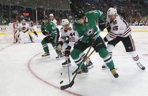 Dallas Stars left wing Remi Elie (40), Chicago Blackhawks defenseman Jan Rutta (44), Dallas Stars center Tyler Pitlick (18) and Chicago Blackhawks center Artem Anisimov (15) fight for control of the puck during the first period of an NHL hockey game, Saturday, Dec. 2, 2017, in Dallas.