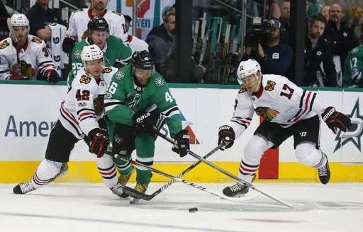 Chicago Blackhawks defenseman Gustav Forsling (42), left, and Chicago Blackhawks left wing Lance Bouma (17), right, try to get the puck from Dallas Stars center Gemel Smith (46) during the first period of an NHL hockey game, Saturday, Dec. 2, 2017, in Dallas.