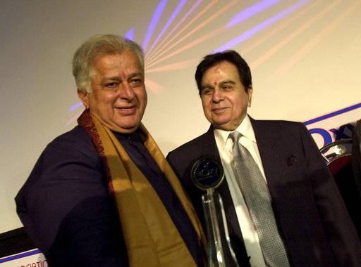 FILE- In this June 2, 2005 file photo, legendary Bollywood actor Dilip Kumar, right, looks at veteran actor Shashi Kapoor, left, at the inauguration of a new cinema in Mumbai, India. Kapoor was felicitated at the event. Kapoor, a prolific Bollywood actor and producer from the 1970s and '80s, died Monday, Dec. 4, 2017 after a long illness. He was 79.