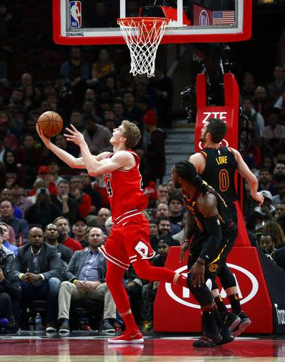 Chicago Bulls' Lauri Markkanen, left, scores on a reverse layup past Cleveland Cavaliers' Kevin Love (0) and Jae Crowder during the first half of an NBA basketball game Monday, Dec. 4, 2017, in Chicago.