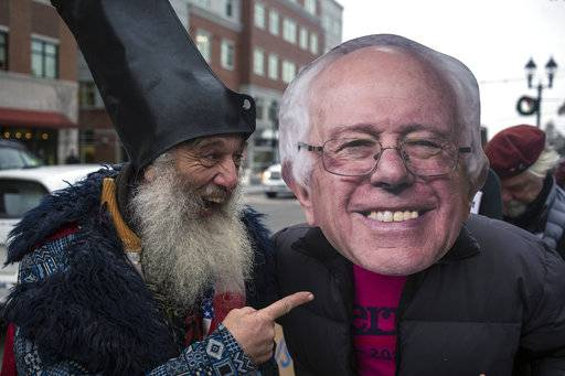 Perennial candidate and performance artist Vermin Supreme talks with a fellow protester in front of Gibson's book store in Concord, N.H., where Hillary Clinton came to sign her latest book on Tuesday, Dec. 5, 2017. (Geoff Forester/The Concord Monitor via AP)
