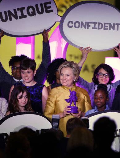 Former Secretary of State Hillary Clinton, center, holds the Believe in Girls award during a fundraising event for the Big Sister Association of Greater Boston, Tuesday, Dec. 5, 2017, in Boston. Clinton was presented with the award during the event.