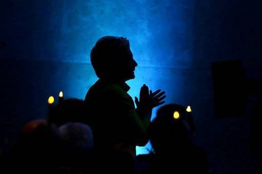 Former Secretary of State Hillary Clinton appears in silhouette as she applauds before taking the stage to speak during a fundraising event for Big Sister Association of Greater Boston, Tuesday, Dec. 5, 2017, in Boston. Clinton was presented with the organization's Believe in Girls award during the event.