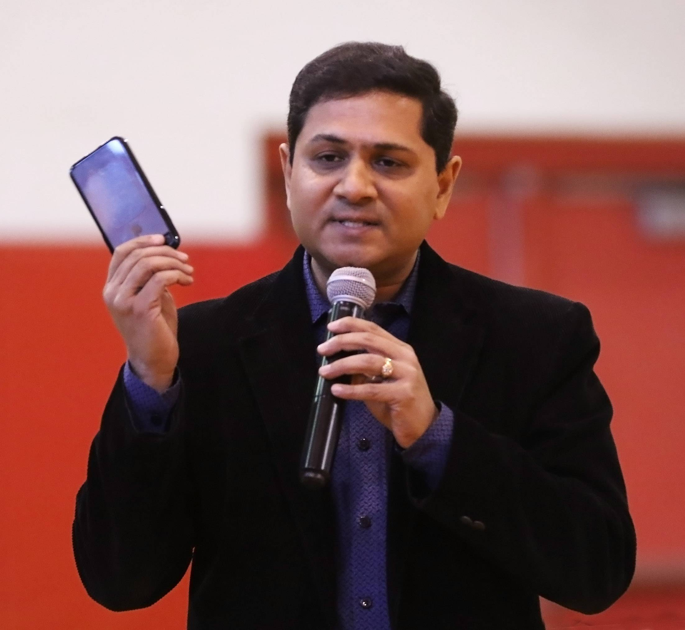 Amazon Web Services leader Hardik Bhatt discusses the computing power of his cellphone before an assembly of students during the Hour of Code initiative Tuesday at St. Anne Parish School in Barrington.