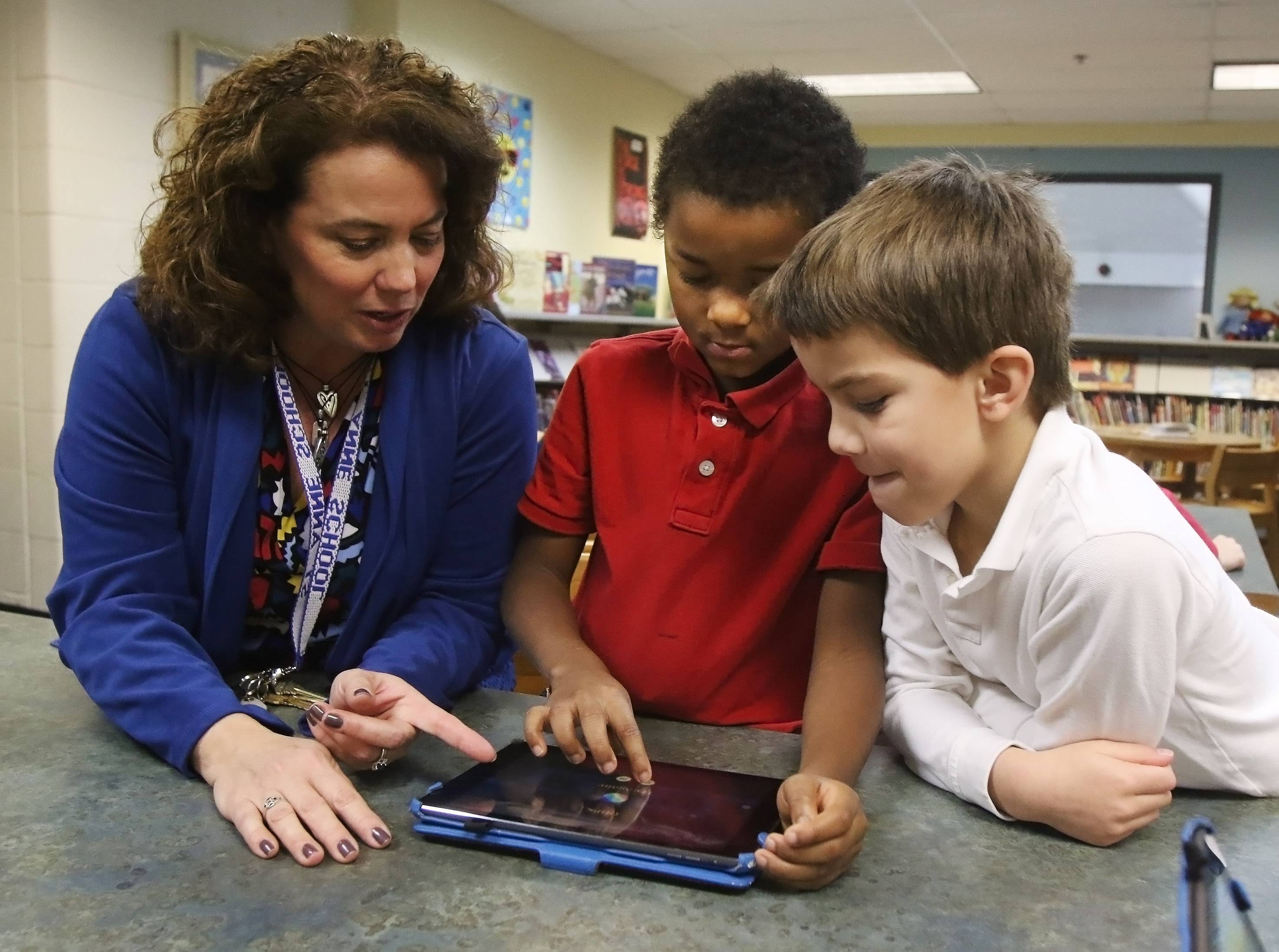 St. Anne's Technology Integration Director Valerie Hughes works with first-graders Kheari Lark and Colton Koehler on Kodable.com during the Hour of Code initiative Tuesday at St. Anne Parish School in Barrington. The mission is to introduce students to computer science and coding.