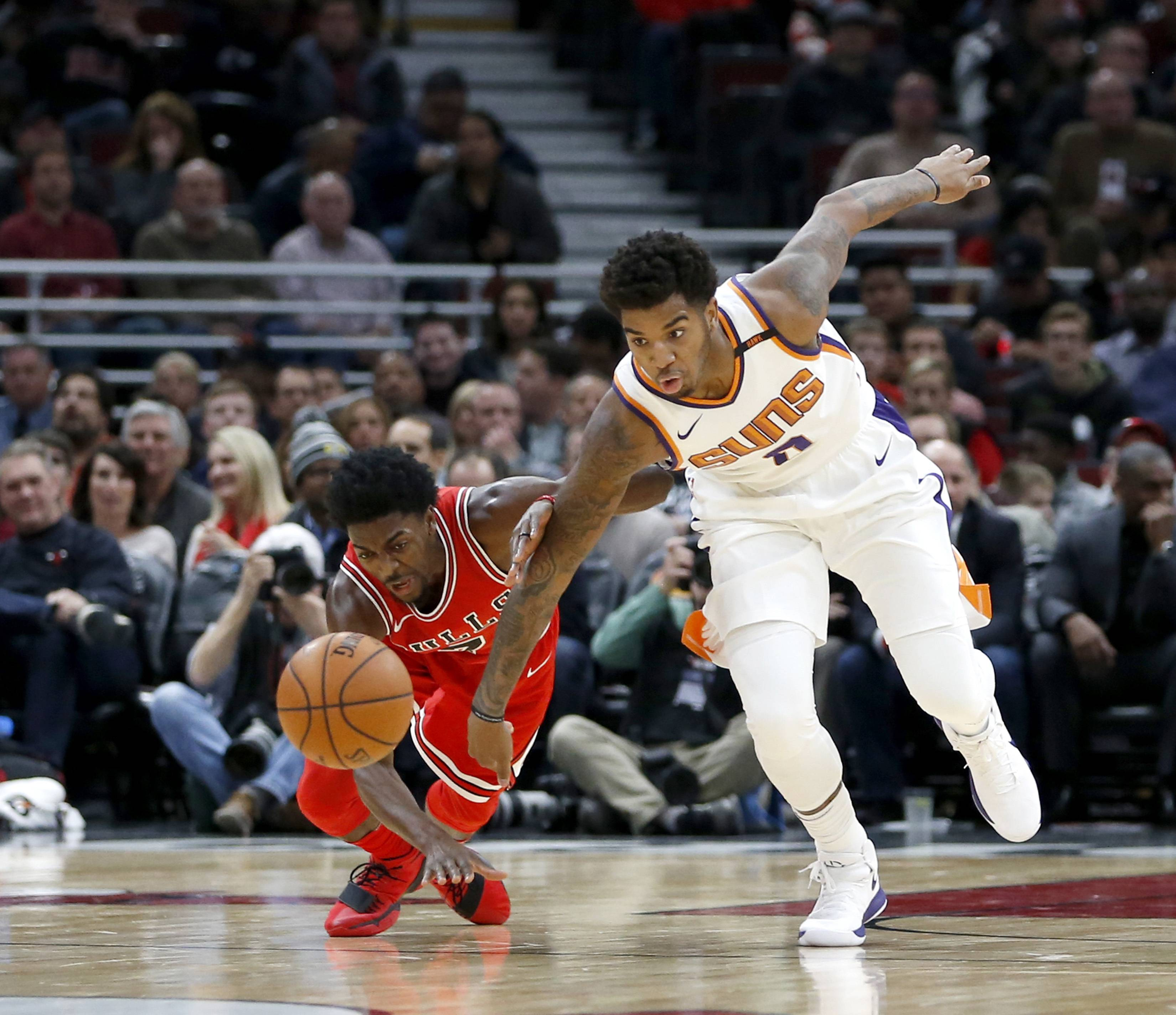 Chicago Bulls' Justin Holiday (7) and Phoenix Suns' Marquese Chriss battle for a loose ball during the first half of an NBA basketball game Tuesday, Nov. 28, 2017, in Chicago.