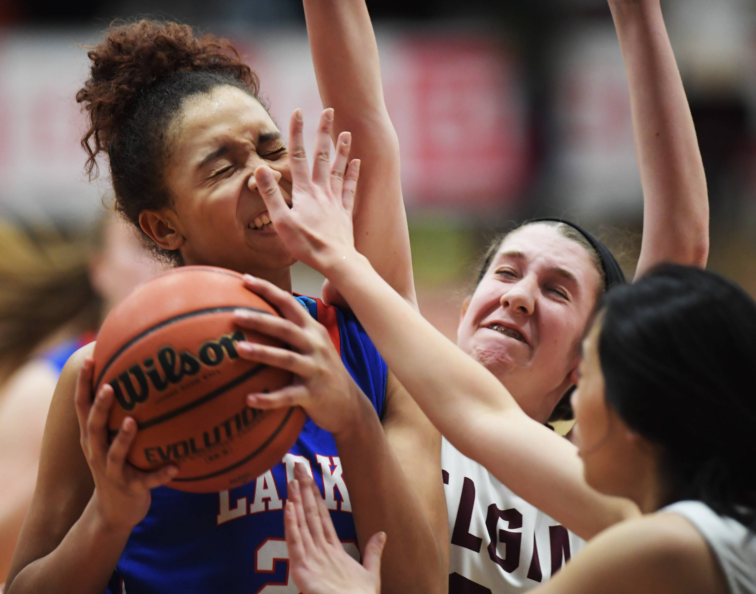 Larkin's Aaliyah Dixon is closely defended by Elgin's Sarah Moskow and Sabrina Chen Tuesday at Chesbrough Field House at Elgin High School.