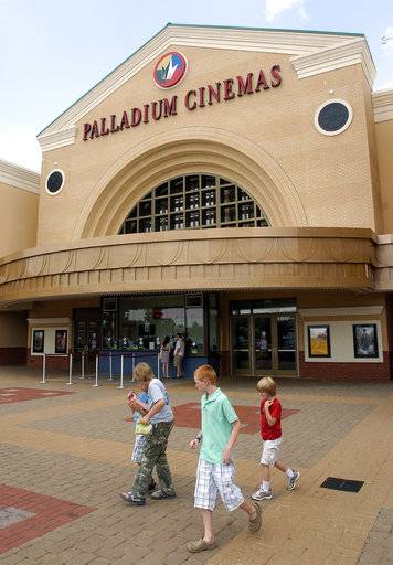 FILE - In this Tuesday July 26, 2011, file photo, people walk past Regal Entertainment's Palladium Cinemas in High Point, N.C. Cineworld is paying $3.61 billion for Regal Entertainment as it expands its global footprint. Cineworld has theaters in several nations, while Regal operates theaters throughout the U.S. (Don Davis Jr./The High Point Enterprise via AP, File)