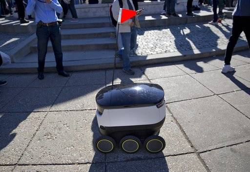 FILE - In this Feb. 20, 2017, file photo, a six-wheeled ground delivery robot, from Starship Technologies, shares the sidewalk with pedestrians at DuPont Circle in Washington, D.C. Delivery robots in San Francisco will need permits before they can roam city sidewalks under legislation approved by supervisors on Tuesday, Dec. 5, 2017. (AP Photo/Pablo Martinez Monsivais, file)