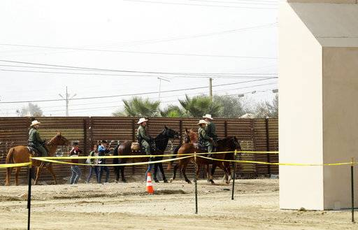FILE - In this Oct. 19, 2017, file photo, a group of people are detained by Border Patrol agents on horseback after crossing the border illegally from Tijuana, Mexico, near prototypes for a border wall, right, being constructed in San Diego. The federal government provided Tuesday, Dec. 5, 2017, the most complete statistical snapshot of immigration enforcement under President Donald Trump, showing Border Patrol arrests plunged to a 45-year low while arrests by deportation officers soared.