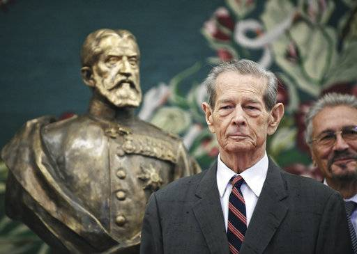 FILE - In this Tuesday, Oct. 25, 2011, file photo, former Romanian King Michael poses next to a bronze sculpture depicting the founder of Romania's royal dynasty, King Carol I, in the country's parliament in Bucharest, Romania. Romania's royal house says former King Michael, who ruled Romania during WWII, has died, Tuesday, Dec. 5, 2017, in Switzerland aged 96.
