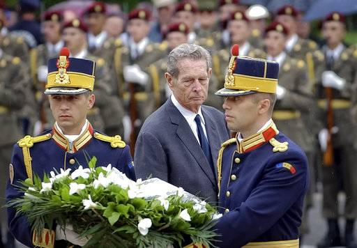 FILE- In this Moday, Aug. 23, 2004 file photo, former King Michael I, center, walks behind soldiers carrying a wreath, in Bucharest, Romania, during ceremonies to celebrate 60 years since Romania switched sides in the WWII joining the Allies in the fight against Hitler. King Michael I, who was forced to abdicate by the communists in the aftermath of World War II, died on Tuesday, Dec. 5, 2017. He was 96.