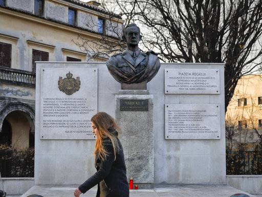 A young woman walks by a statue of former Romanian King Michael, in Bucharest, Romania, Tuesday, Dec. 5, 2017. Romania's royal house said that former King Michael, who ruled Romania during WWII,  died, Tuesday, in Switzerland, aged 96.