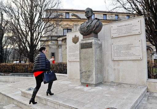A woman places a candle next to a statue of former Romanian King Michael, in Bucharest, Romania, Tuesday, Dec. 5, 2017. Romania's royal house said that former King Michael, who ruled Romania during WWII,  died, Tuesday, in Switzerland, aged 96.